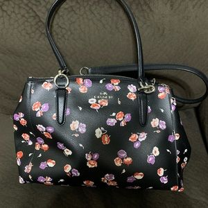 Black COACH bag with red and purple flowers.